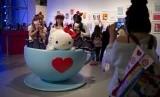 Pengunjung berfoto dengan cangkir besar bergambar Hello Kitty.
