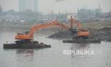 Petugas dengan alat berat mengeruk endapan lumpur di sungai Ciliwung di kawasan Banjir Kanal Barat (BKB), Jakarta, Ahad  (24/9).