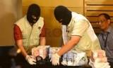 Petugas KPK memperlihatkan barang bukti berupa uang hasil operasi tangkap tangan (OTT).  (ilustrasi)