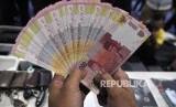 Petugas memperlihatkan barang bukti uang palsu saat rilis pengungkapan jaringan produksi dan peredaran uang palsu di gedung Bareskrim Polri, Jakarta, Rabu (18/10).