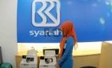Petugas menghitung uang nasabah di salah kantor Bank BRI Syariah, Jakarta, Kamis (20/8).