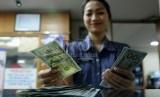 Petugas menghitung uang pecahan Dolar AS di salah satu tempat penukaran uang, Jakarta, Kamis (23/4).  (Republika/Prayogi)