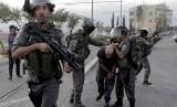 Polisi perbatasan Israel menahan seorang pengunjuk rasa Palestina dalam bentrokan di Shuafat, sebuah daerah pinggiran Arab Yerusalem.
