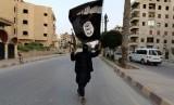 Prajurit ISIS mengibarkan panji kebesarannya.