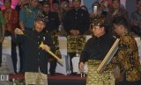 Presiden Joko Widodo (kiri) mendapat cendera mata dari Ketua Umum Ikatan Pencak Silat Indonesia (IPSI), Prabowo Subianto (kedua kanan) saat penutupan Kejuaraan Pencak Silat Internasional di GOR Lila Bhuana, Denpasar, Bali, Kamis (8/12).