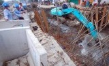 Sebuah alat berat melakukan pengerukan endapan di dasar sungai pada proyek gorong-gorong (box culvert) tahap II kawasan Banyuurip, Surabaya