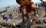Sejumlah orang tua dan anak-anak berenang di tepian pantai wisata Tanjung Pasir, Kabupaten Tangerang, Banten