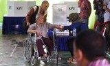 Seorang disabilitas mengikuti proses pencoblosan Pilkada DKI Jakarta di TPS 6, Rawa Barat, Jakarta, Rabu (15/2).