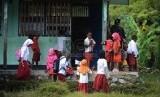 Seorang guru bersama murid membersihkan kelas sebelum melakukan kegiatan belajar mengajar di SD Athahiriyah Yapis Walesi, Wamena, Kabupaten Jayawijaya, Papua. ilustrasi