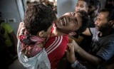 Seorang pemuda Palestina berduka memegang mayat adiknya, salah satu dari empat anak laki-laki yang tewas dalam serangan Israel di Gaza.