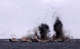 Serpihan kapal berhamburan ke udara saat penenggelaman kapal penangkap ikan ilegal di perairan Bitung, Sulawesi Utara, Senin (22/2)