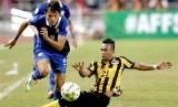 Striker Thailand, Adisak Kraisorn (kiri) mengejar bola melewati hadangan bek Malaysia, Muhammad Azmi, pada pertandingan final leg pertama Piala AFF 2015 di Stadion Rajamangala, Bangkok, Rabu (17/12). Laga itu dimenangkan Thailand 2-0.