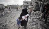 Wanita Palestina di Jalur Gaza menggendong anaknya melewati reruntuhan bangunan yang hancur akibat rudal Israel.