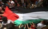 Warga Gaza membentangi bendera Palestina.