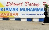 Warga melintas di depan spanduk penyambutan peserta Muktamar ke-47 Muhammadiyah di Kampus Universitas Muhammadiyah (Unismuh) Makassar, Sulawesi Selatan, Ahad  (26/7).