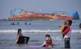 Wisatawan menikmati suasana Pantai Pangandaran dengan latar Bangkai Kapal FV Viking di pesisir Pantai Timur Pangandaran