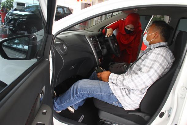 Pramuniaga menjelaskan fitur mobil kepada konsumen di diler Toyota Auto2000, Malang, Jawa Timur.
