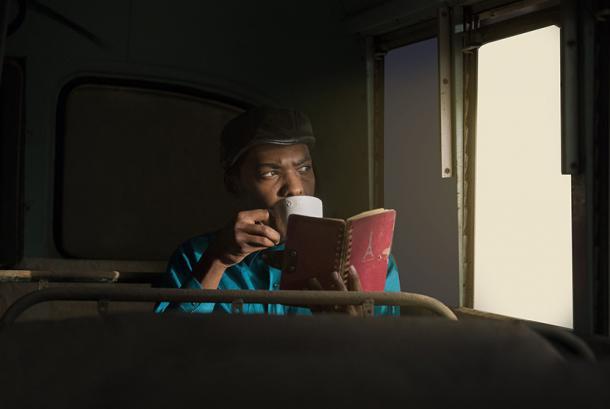 Seorang pria meminum kopi dalam kendaraan. Ilustrasi