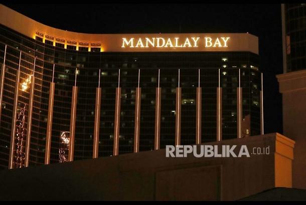 Polisi setempat berlindung dari balik mobil di dekat  Mandalay Bay, Las Vegas Strip, Ahad (1/10) waktu setempat.