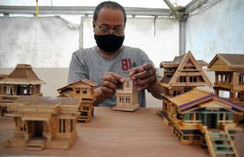 Perajin mengerjakan pembuatan kerajinan miniatur rumah dari bahan stik es krim saat Pesta Rakyat di Kota Bogor, Jawa Barat.