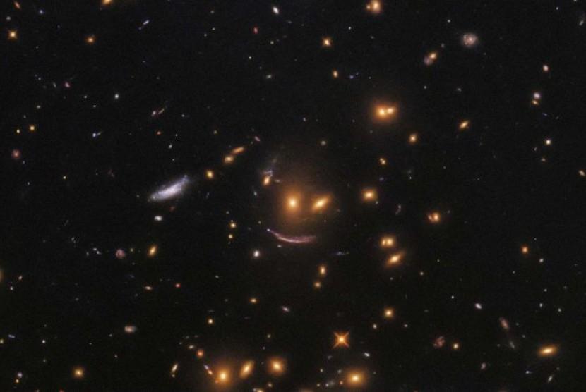 'Bintang tersenyum yang tertangkap teleskop Hubble, disebabkan oleh cahaya yang melintasi suatu objek besar dengan daya gravitasi tinggi sehingga membuatnya melengkung.