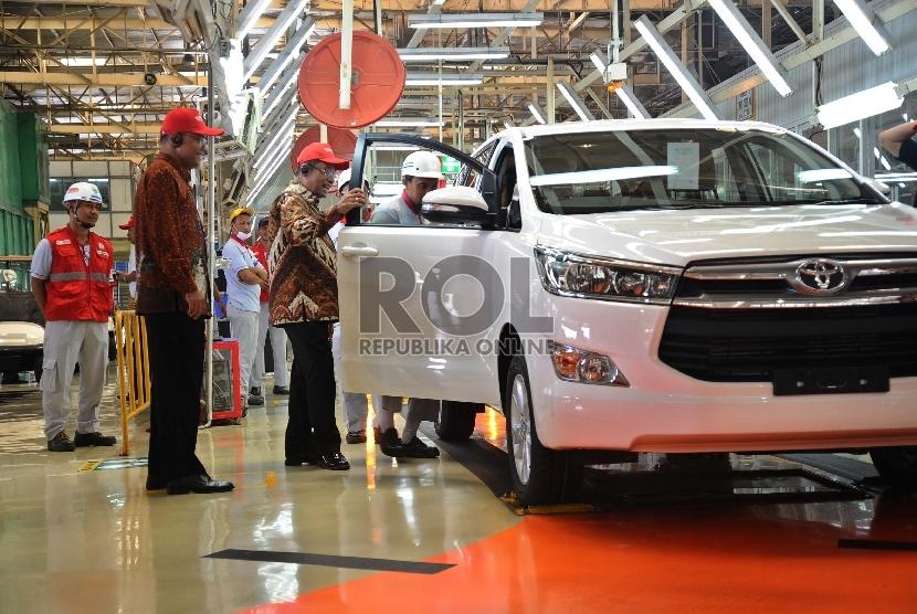 (dari kiri) Wakil Presiden Toyota Motor manufacturing Indonesia (TMMIN) Warih Andang Tjahyono, Menteri Perindustrian Saleh Husin melihat pengecekan kualitas mobil usai line off Toyota Innova di pabrik PT TMMIN, Karawang, Jawa Barat, Selasa (24/11).