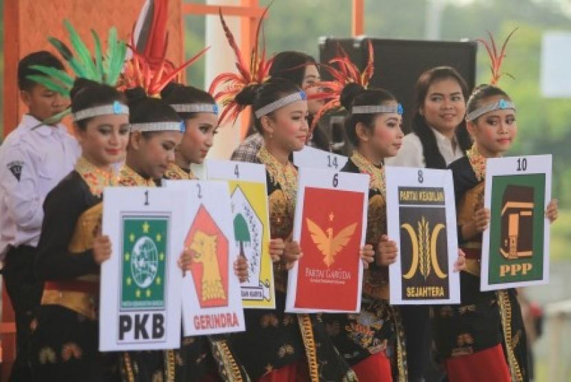 (Ilustrasi) Sejumlah penari membawa lambang partai politik.