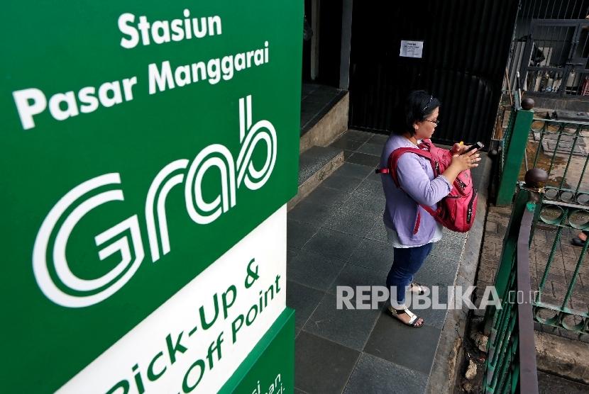 [ilustrasi] Seorang wanita sedang mengecek ponselnya di sebelah banner iklan Grab di Stasiun Manggarai, Jakarta.