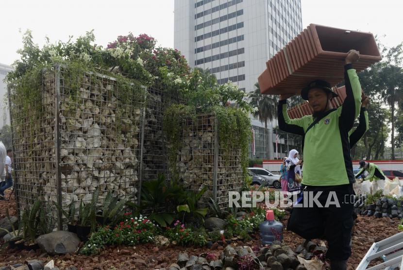 Petugas membawa pot di dekat instalasi batu gabion di Bundaran HI, Jakarta, Jumat (23/8).