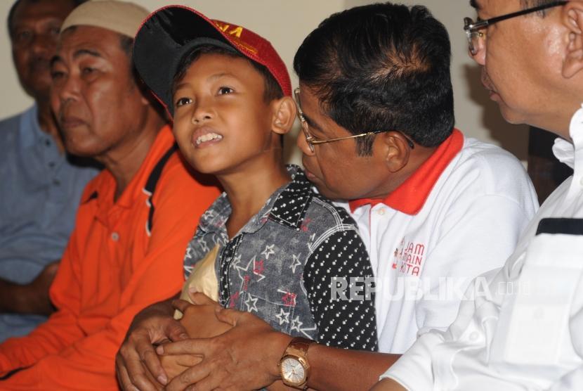 Menteri Sosial Idrus Marham memangku  anak tiri dari Alm Aiptu Anumerta Denny Setiawan saat melakukan kunjungan ke kediaman  Denny Setiawan di Cipayung, Jakarta Timur, Kamis (10/5).
