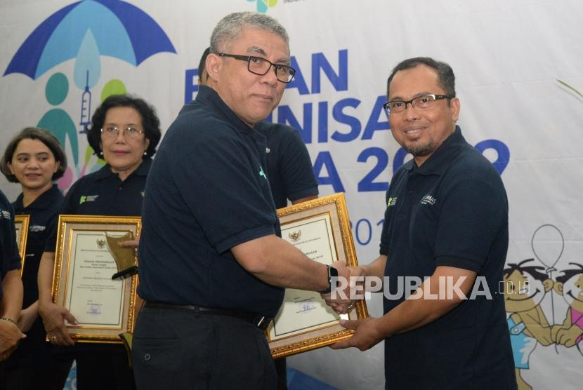 Sekjen Kemenkes Oscar Primadi memberikan penghargaan kepada Wakil Pemimpin Redaksi Republika Nur Hasan Murtiadji di sela acara Pekan Imunisasi Dunia 2019 di Kantor Kemenkes, Jakarta, Selasa (23/4).