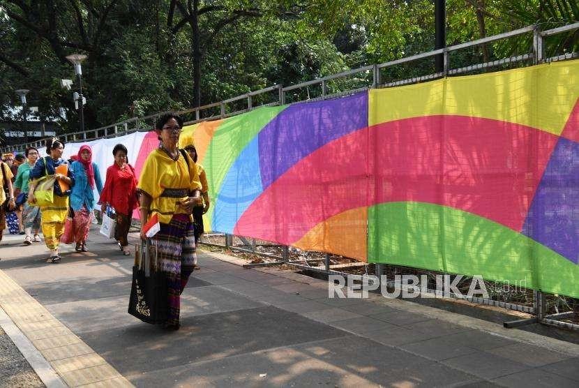 Pengunjung melintas mengunakan pakaian adat di kompleks Gelora Bung Karno Jakarta, Sabtu (18/8).
