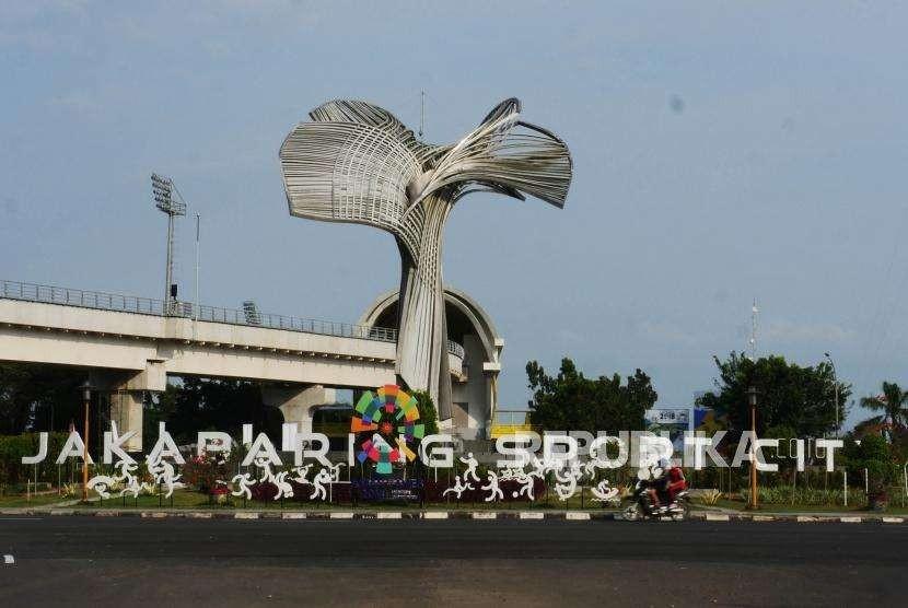 Pengendara sepeda motor melintas di bundaran Jakabaring Sport City, Palembang, Jumat (3/8).