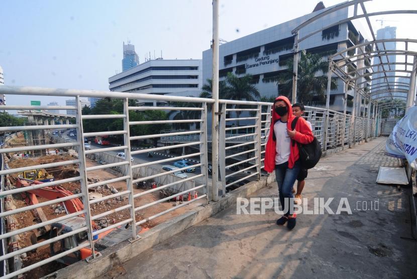 Warga melintasi Jembatan Penyeberangan Orang (JPO) yang terdampak pembangunan LRT di kawasan Kuningan, Jakarta Selatan, Ahad (22/7).