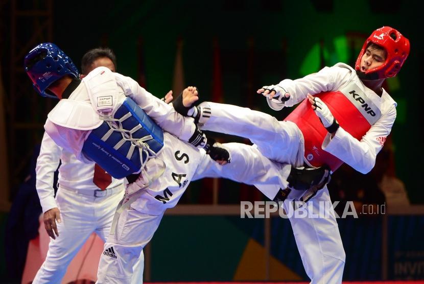 Atlet taekwondo Indonesia Dinggo Ardian (merah) melancarkan tendangan ke arah lawannya dari Malaysia Rozaimi Rozali (biru) pada babak perempat final pertandingan taekwondo kelas -80 kg pada Turnamen Invitasi Asian Games 2018 di JI Expo Kemayoran, Jakarta, Ahad (11/2).