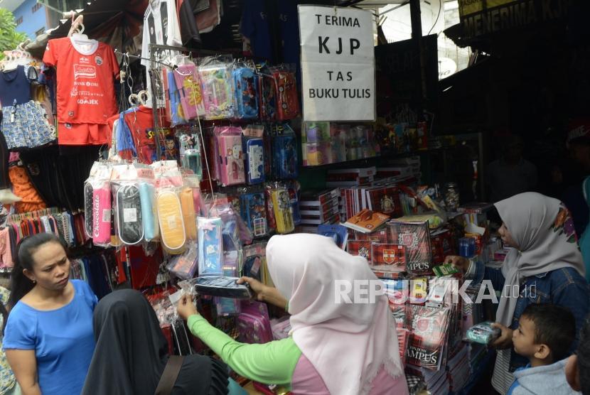 Sejumlah calon pembeli saat mencari perlengkapan sekolah untuk anaknya di Pasar Jatinegara, Jakarta, Ahad (14/7).