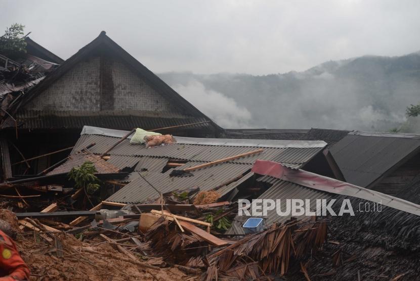 Longsoran rumah menutupi rumah penduduk di dusun Cimapag, Desa Sinaresmi, Cisolok, Sukabumi, Jawa Barat, Selasa (1/1).