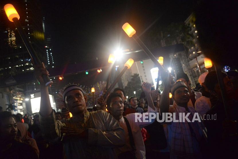 Sejumlah peserta mengikuti pawai obor elektrik pada Jakarta Muharram Festival di Jalan MH Thamrin, Jakarta, Sabtu (31/8).