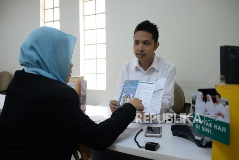 Petugas melayani nasabah di salah satu kantor Bank Danamon Syariah di Jakarta, Selasa (16/10).