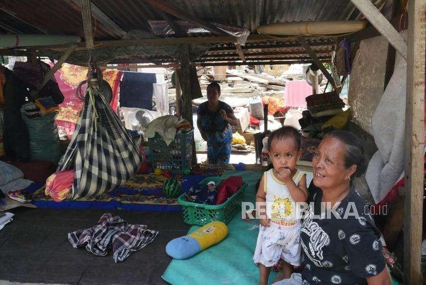 Seorang ibu, bersama cucuknya terpaksa harus tinggal di tenda pengungsi di depan rumahnya di Desa Salua, Kecamatan Sigi, Sulawesi tengah, kamis (10/10).