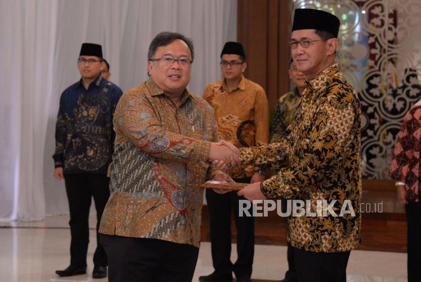 Menteri PPN/Kepala Bappenas sekaligus Sekretaris Dewan Pengarah Komite Nasional Keuangan Syariah (KNKS) Bambang Brodjonegoro menyerahkan berkas acara kepada Ventje Rahardjo Soedigno  usai memimpin pengambilan sumpah jabatan dan pelantikan direktur eksekutif dan para direktur KNKS di Jakarta, Kamis (3/1).