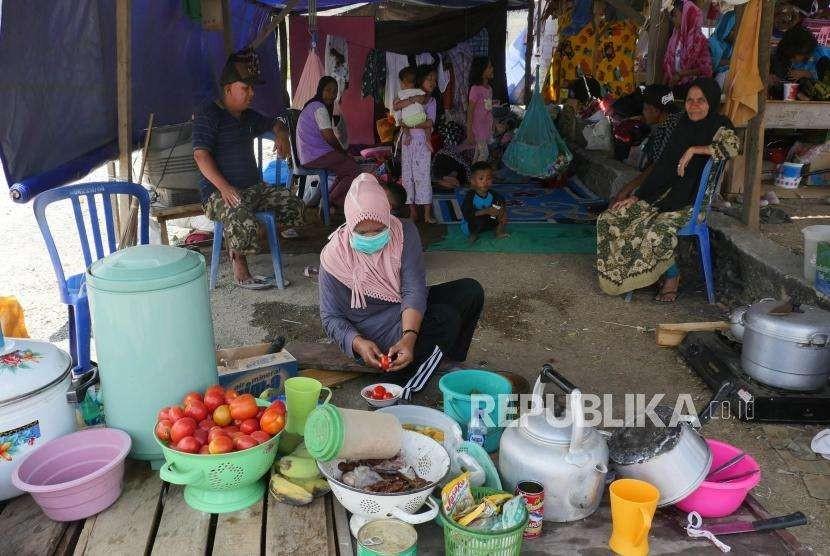 Seorang ibu mempersiapkan bahan makanan untuk dimasak di dapur umum darurat untuk keluarganya di tempat pengungsian Duyu, Palu Barat, kecamatan Tatanga, Selasa (9/10).