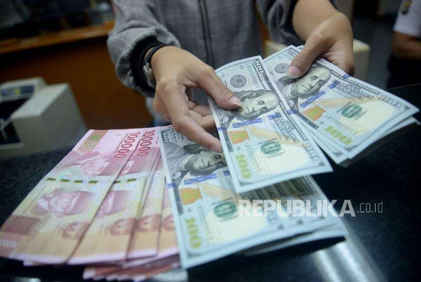 Petugas menghitung pecahan dolar Amerika Serikat dan rupiah di salah satu gerai penukaran mata uang asing di Jakarta,Ahad (2/9).
