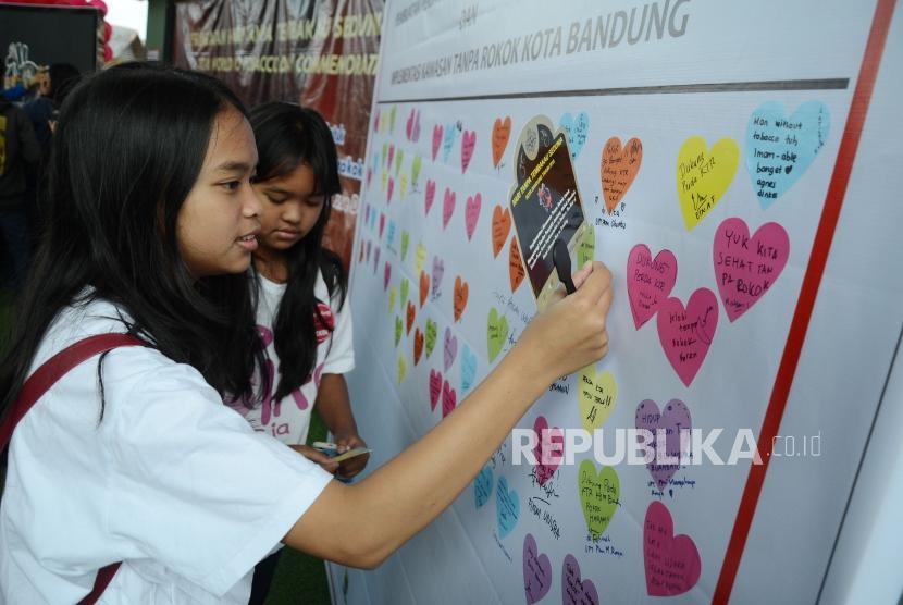 Pengunjung menempelkan pesan dan dukungan untuk pembuatan perda dan implementasi kawasan tanpa rokok pada pameran seni instalasi dalam rangka memperingati Hari Tanpa Tembakau Sedunia yang digelar Pemerintah Kota Bandung, di Taman Film, Kota Bandung, Ahad (27/5).