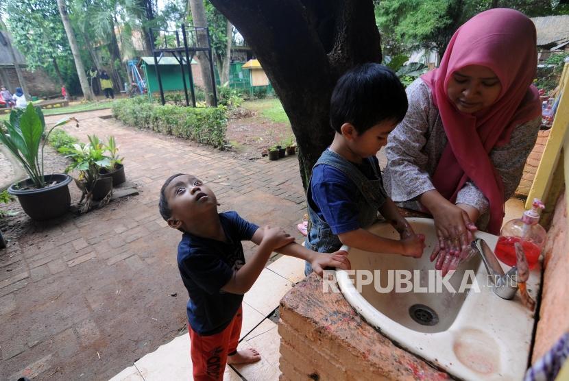Salah seorang guru mengajarkan mencuci tangan kepada murid di Sekolah Citra Alam, Jagakarsa, Jakarta, Senin (18/12).