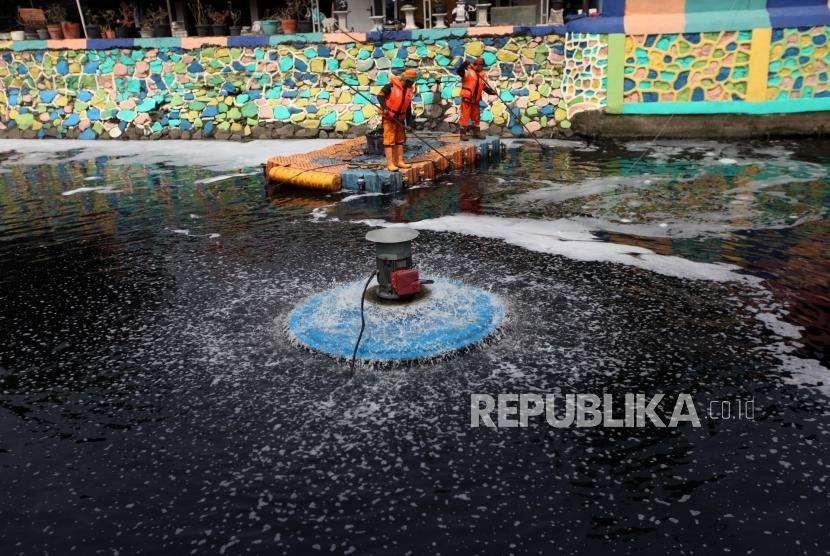 Petugas Penanganan Prasarana dan Sarana Umum (PPSU) membersihkan sampah di tengah pengoperasian Nano Bubble dan Aerator di Kali Sentiong atau Kali Item, Jakarta, Kamis (2/8).