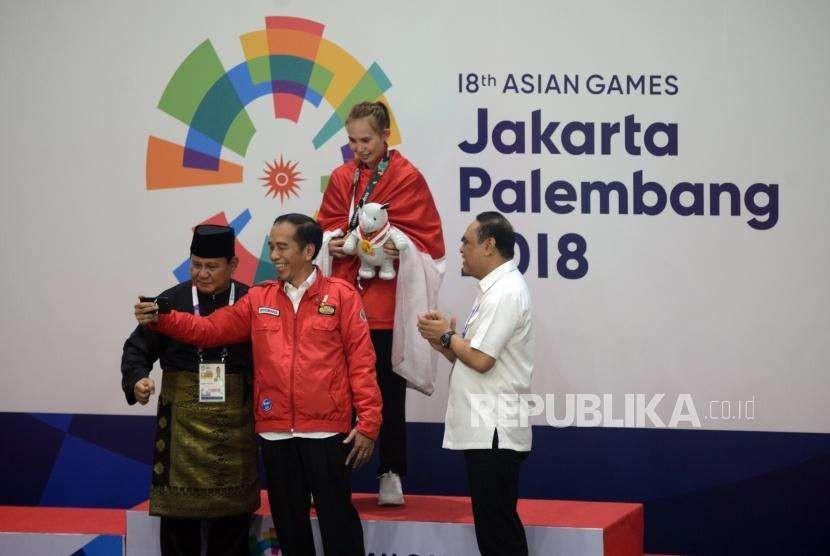 Presiden Joko Widodo (kiri) bersama Ketua Umum Pengurus Besar Ikatan Pencak Silat Seluruh Indonesia Prabowo Subianto (kedua kiri) usai memberikan medali kepada pesilat Indonesia Wewey Wita usai pertandingan cabang olahraga silat Asian Games 2018 di Padepokan Pencak Silat TMII, Jakarta, Rabu (29/8).
