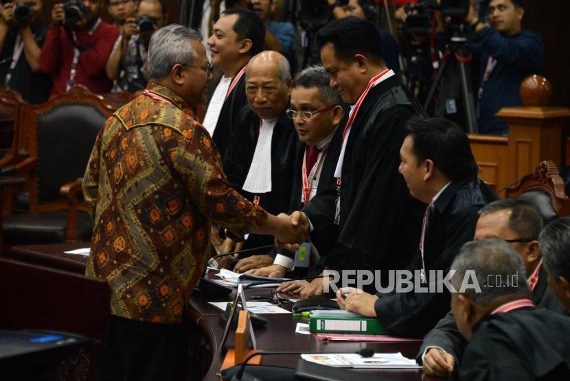 Ketua KPU Arief Budiman bersalaman dengan Ketua Tim Hukum Joko Widodo-Ma'ruf Amin, Yusril Ihza Mahendra, sebelum dimulainya sidang lanjutan Perselisihan Hasil Pemilihan Umum (PHPU) Pemilihan Presiden (Pilpres) 2019 di Gedung Mahkamah Konstitusi, Jakarta, Selasa (18/6).