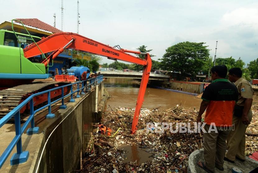 Petugas Dinas Kebersihan DKI Jakarta saat membersihkan sampah yang menumpuk di Pintu Air Manggarai, Jakarta, Senin (12/11).