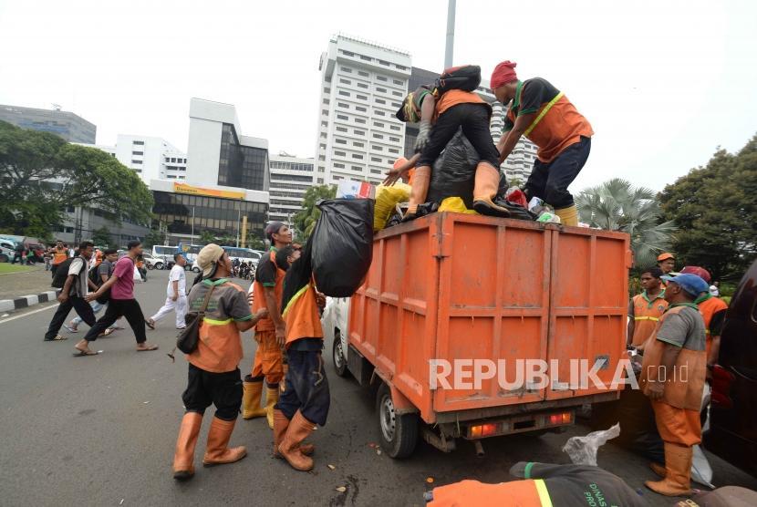 Petugas PPSU membersihkan sampah pasca aksi reuni 212 di kawasan Tugu Tani, Jakarta, Ahad (2/12).